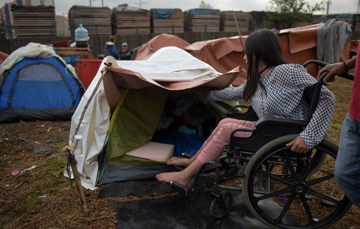 Migrante venezolana Laurymar López, en silla de ruedas, es fotografiada en un campamento improvisado cerca de una terminal de autobuses en Bogotá en noviembre de 2018. - Como han informado la Organización de las Naciones Unidas para las Migraciones (OIM) y el Alto Comisionado de las Naciones Unidas para los Refugiados (ACNUR), los refugiados y migrantes de Venezuela en todo el mundo han llegado a los tres millones. (Foto de Raúl ARBOLEDA/AFP) (El crédito de la foto debe ser RAUL ARBOLEDA/AFP/Getty Images)