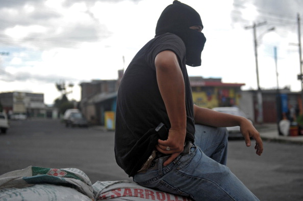 En esta foto de archivo, un hombre encapuchado con un arma de fuego hace guardia en la entrada del barrio de Castanas, en las afueras del sur de la Ciudad de Guatemala, para prevenir un ataque de una pandilla local. Los residentes de Castanas fueron amenazados y extorsionados por pandilleros, por tal motivo,  organizaron su propia banda armada en defensa propia. Contrariamente a lo que se pretendía, la ayuda de Estados Unidos está ayudando a las pandillas y perjudicando a los ciudadanos honestos de Guatemala. (JOHAN ORDONEZ/AFP/Getty Images)