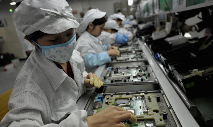 Trabajadores chinos ensamblan componentes electrónicos en una fábrica en la ciudad de Shenzhen, en la provincia de Guangzhou, China, el 26 de mayo de 2010. (AFP/AFP/Getty Images)