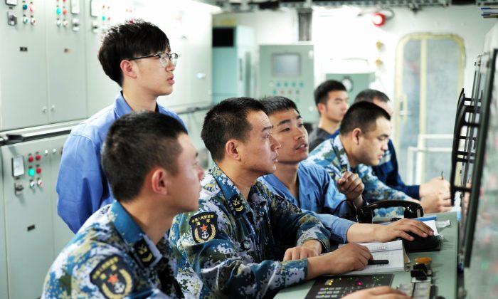 Marineros del Ejército Popular de Liberación trabajando a bordo del primer portaaviones de fabricación nacional de China, durante su primera prueba marítima en el mar, el 18 de mayo de 2018. (AFP/Getty Images)