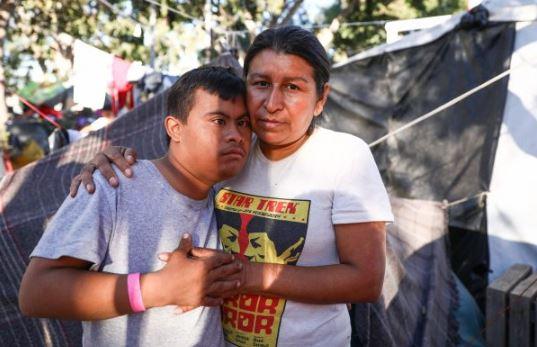 María Luisa Cáceres, de 42 años, con su hijo, ambos de Honduras, en el campamento para migrantes en el complejo deportivo Benito Juárez en Tijuana, México, el 26 de noviembre de 2018. (Charlotte Cuthbertson/La Gran Época)