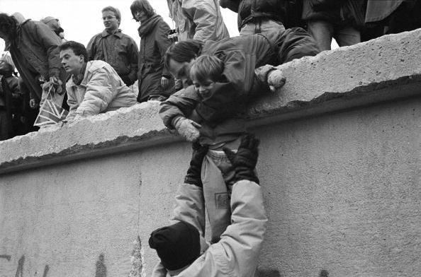 Berlineses del Este escalan el Muro de Berlín para celebrar el fin efectivo de la partición de la ciudad, 31 de diciembre de 1989. (Steve Eason/Hulton Archive/Getty Images)