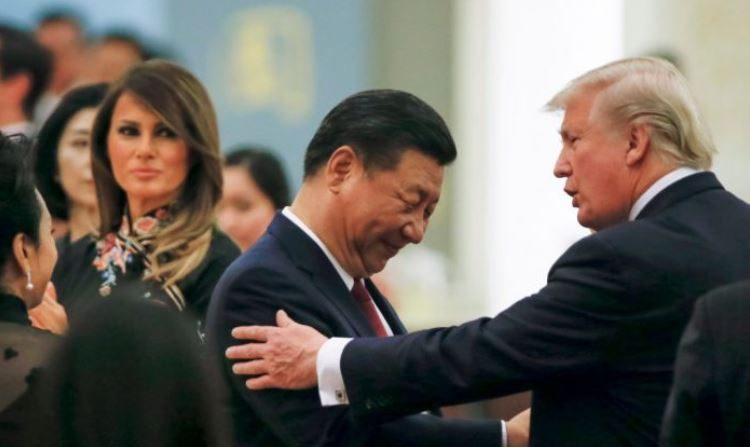 El presidente de los Estados Unidos, Donald Trump, habla con el mandatario de China, Xi Jinping, mientras la Primera Dama de los Estados Unidos, Melania Trump observa, durante una cena de estado en el Gran Palacio del Pueblo en Beijing el 9 de noviembre de 2017. (THOMAS PETER/AFP/Getty Images)