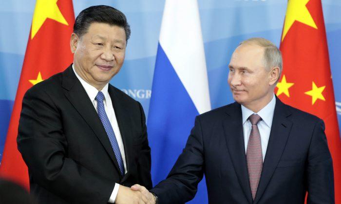 El presidente de Rusia, Vladimir Putin (Der.), da la mano a su homólogo chino Xi Jinping durante una ceremonia de firma tras las conversaciones ruso-chinas en el marco del Foro Económico del Este en Vladivostok, el 11 de septiembre de 2018. (SERGEI CHIRIKOV/AFP/Getty Images)