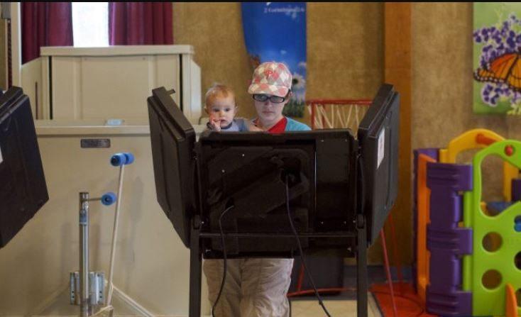 Una mujer sostiene a su hijo de 8 meses mientras vota en la mesa electoral de la Iglesia Metodista Unida de Trucksville durante las elecciones primarias de Pensilvania 2018 en Trucksville, Pensilvania, el 15 de mayo de 2018. (Mark Makela / Getty Images)