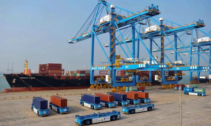 Camiones transfieren contenedores en un muelle de carga automatizado en Qingdao, en la provincia oriental de Shandong, China, el 24 de octubre de 2018. (STR/AFP/Getty Images)