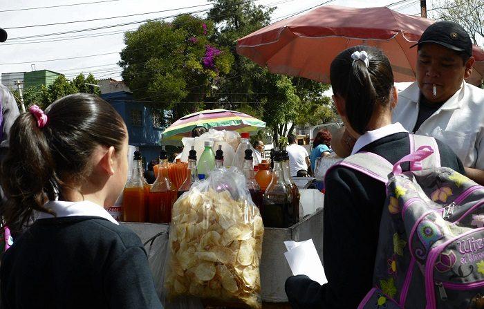 Unas niñas estudiantes compran frituras hoy, lunes 10 de enero de 2011, afuera de un colegio en la capital mexicana. La venta de comida chatarra es regulada desde hoy en los colegios de nivel básico en México como una medida para combatir el sobrepeso infantil, que afecta a un 30% de los niños y al 70% de los adultos. EFE/Mario Guzmán