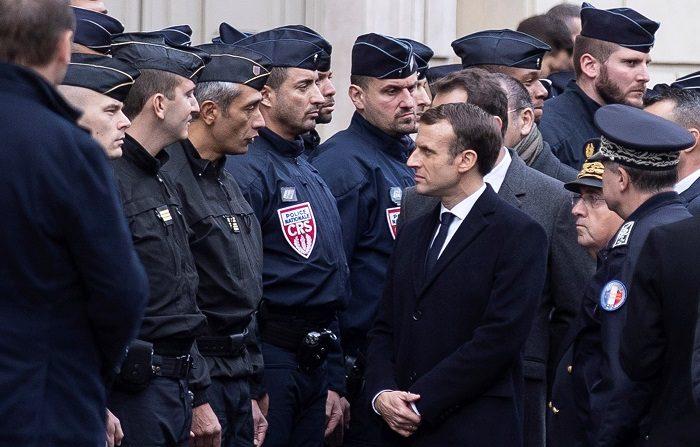 El presidente francés Emmanuel Macron (dcha) habla con la policía tras los disturbios de ayer en París. EFE/EPA/ETIENNE LAURENT