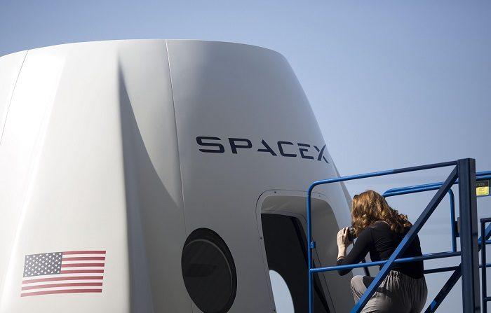 """Una periodista toma fotos del exterior de una cápsula espacial que en un futuro llevará astronautas de la empresa SpaceX, durante un recorrido de prensa el 13 de agosto de 2018, mientras decenas de ingenieros continúan sus trabajos en un enorme hangar de SpaceX situado en la ciudad de Hawthorne (EE.UU). A escasos metros de la cápsula con la que viajará por primera vez al espacio el astronauta Victor Glover, y con la honestidad e inocencia de un novato, resumió la emoción que se respira en la sede de SpaceX: """"¿Escuchan todo ese ruido al fondo? Eso es que están pasando cosas increíbles"""". EFE/Armando Arorizo"""