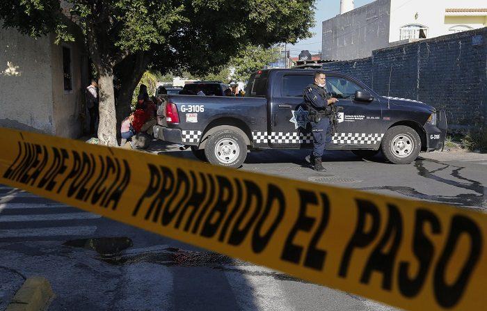 Policías municipales custodian una finca donde fueron hallados cuatro cadáveres hoy, viernes 3 de agosto de 2018, en Guadalajara (México). Los cuerpos de cuatro personas, entre ellos una mujer, fueron encontrados hoy en una fosa dentro de una finca ubicada una céntrica colonia del municipio de Guadalajara, en el estado de Jalisco, oeste de México, informaron hoy fuentes de la policía municipal. EFE/Francisco Guasco