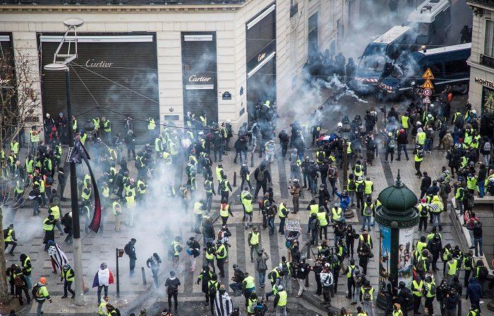 Chalecos amarillos se enfrentan a las fuerzas policiales durante una manifestación cerca de los Campos Elíseos en París. EFE
