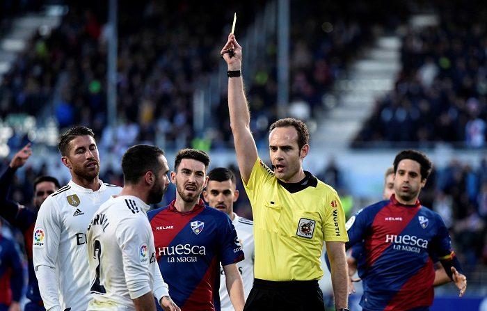 El árbitro Mario Melero muestra tarjeta amarilla al defensa del Real Madrid Daniel Carvajal, durante el partido contra el Huesca en la decimoquinta jornada de Liga que disputan en el estadio oscense de El Alcoraz. EFE/Javier Blasco