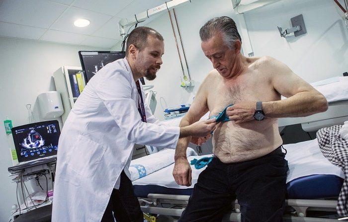 El doctor Jorge Pagola, investigador del VHIR, coloca al paciente Meriton Bacuña, un chaleco Holter -aparato que registra la actividad del corazón- para detectar la causa de los ictus en un grupo de pacientes que padecen fibrilación auricular, un tipo de arritmia muy difícil de localizar. EFE/ Enric Fontcuberta