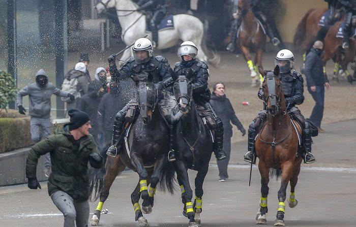 """Policías a caballo persiguen a manifestantes de asociaciones flamencas de derecha durante la manifestación """"Marcha contra Marrakech"""" cerca de la sede de las instituciones europeas en Bruselas, Bélgica, el 16 de diciembre de 2018. (Protestas, Bélgica, Bruselas) EFE/EPA/JULIEN WARNAND"""