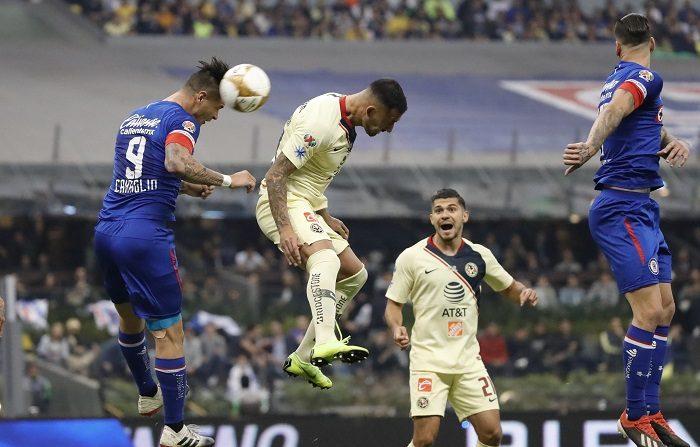 El jugador de Cruz Azul Milton Caraglio (i), pelea por el balón con Víctor Aguilera (c), de América hoy, durante el juego de vuelta de la final del torneo mexicano de fútbol, celebrado en el estadio Azteca en Ciudad de México (México). EFE/José Méndez.