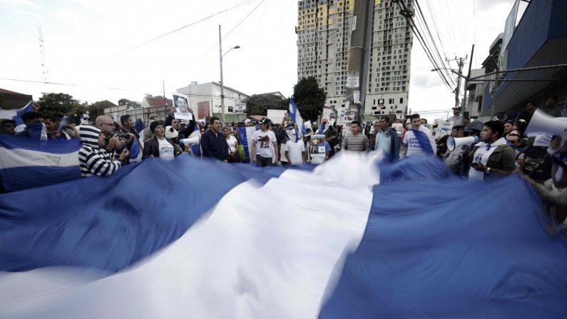 """Decenas de nicaragüenses que han tenido que huir a Costa Rica debido a la crisis sociopolítica en su país, se manifiestan, frente a la embajada de Nicaragua, en San José (Costa Rica), para protestar contra el Gobierno de Daniel Ortega y las violaciones a los derechos humanos. Con cánticos de """"¡Justicia! ¡Justicia!"""", los nicaragüenses, ataviados con los colores de la bandera de su país, realizaron la protesta pacífica por alrededor de dos horas. EFE/Jeffrey Arguedas"""