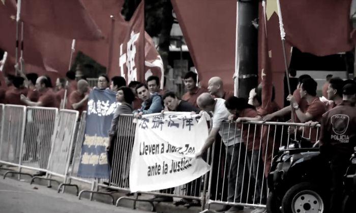 """Nueve practicantes argentinos de Falun Dafa cuelgan dos banderas en las vallas de contención, que dicen """"Detengan la persecución a Falun Gong en China"""" y """"Lleven a Jiang Zemin ante la justicia"""" en español y chino. Los practicantes están rodeados de simpatizantes del Partido Comunista Chino enviados a dar la bienvenida al mandatario chino Xi Jinping. (Captura de pantalla de YouTube)"""