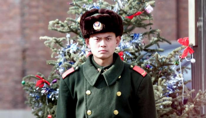 Un efectivo de la Policía Armada Popular de China hace guardia frente a un árbol de Navidad delante de un complejo diplomático en Beijing, China, el 21 de diciembre de 2000. (Goh Chai Hin/AFP/Getty Images)
