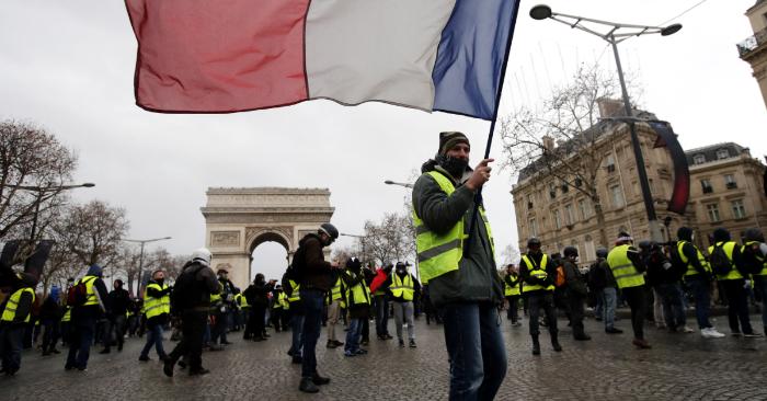 Un manifestante de los chalecos amarillos ondea una bandera tricolor francesa durante una protesta en París. (EFE)