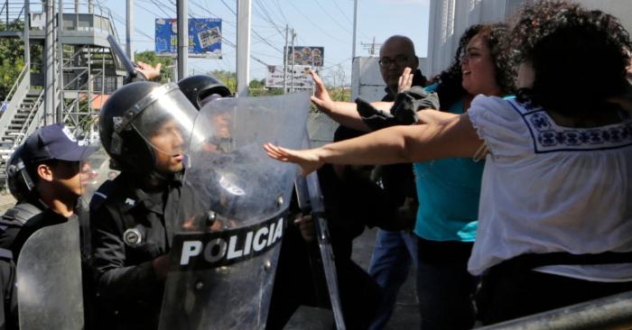 Policías antidisturbios arremeten contra periodistas en los alrededores de la estación de policía 'Plaza El Sol' mientras el periodista nicaragüense Carlos Fernando Chamorro (fuera de encuadre) intentaba hablar con el comisionado principal de la Policía Nacional, en Managua, el 15 de diciembre de 2018. (Foto de INTI OCON/AFP/Getty Images)