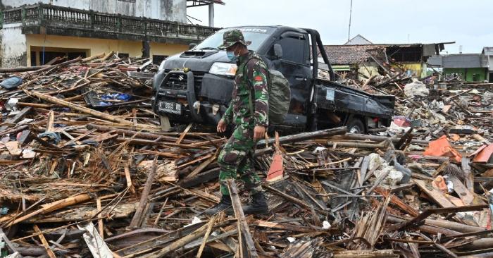 Un soldado camina entre los escombros dejados por eltsunami en la aldea de Sumur, Pandeglang, provincia de Banten, el 25 de diciembre de 2018, tres días después de que el tsunami golpeara la costa occidental de la isla indonesia de Java. (Foto de ADEK BERRY/AFP/Getty Images)