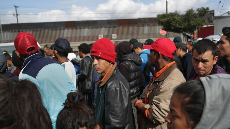 Miembros de la caravana de migrantes esperan por comida, cerca de la valla fronteriza de los Estados Unidos y México el 1 de diciembre de 2018 en Tijuana, México. Las autoridades cerraron un refugio junto a la cerca por insalubre y llevaron a los miles de migrantes a otra instalación, más lejos de la frontera. (John Moore/Getty Images)