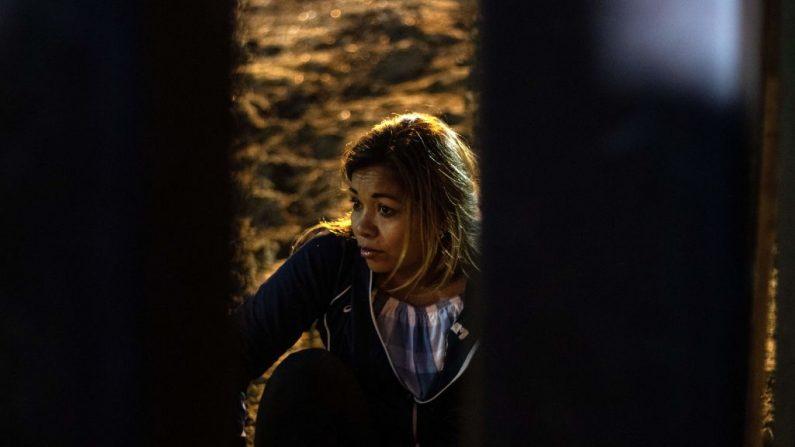Una mujer que ha estado viajando en una caravana de migrantes centroamericanos que esperan entrar ilegalmente a Estados Unidos, observa mientras ve otras personas subiendo la barrera de metal que separa a México de Estados Unidos en las Playas de Tijuana el 3 de diciembre de 2018. (Guillermo Arias / AFP/ Getty Images)