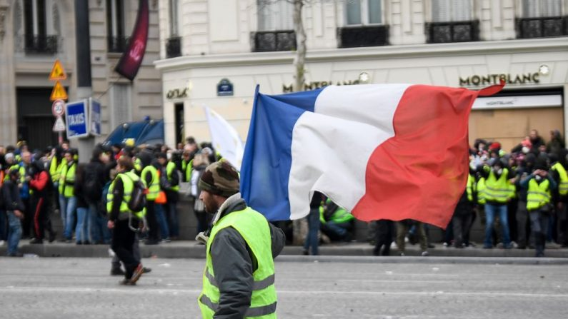 Un manifestante con 'chaleco amarillo' (gilet jaune) sostiene una bandera nacional francesa el 8 de diciembre de 2018 cerca del Arco del Triunfo (Arc de Triomphe) en París. (ERIC FEFERBERG/AFP/Getty Images)