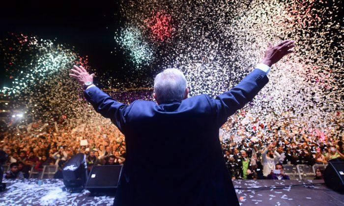 """El presidente de México Andrés Manuel López Obrador (C), por el partido """"Juntos haremos historia"""", aclama a sus seguidores en la Plaza Zócalo luego de ganar las elecciones, en la ciudad de México, 1 de julio de 2018. (Pedro Pardo/AFP/Getty Images)"""