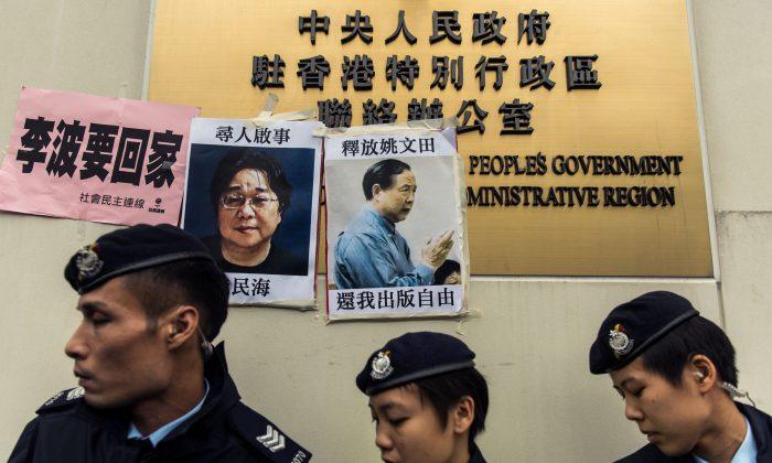 La policía frente a anuncios de las personas desaparecidas Gui Minhai (izq), uno de los cinco libreros de la editorial Mighty Current, y Yau Wentian (der), un editor de Hong Kong quien fue encarcelado el año pasado a 10 años mientras se preparaba para publicar un libro crítico del liderazgo chino. Los anuncios están publicados sobre un cartel de la Oficina de Enlace de China en Hong Kong el 3 de enero de 2016. (ANTHONY WALLACE/AFP/Getty Images)