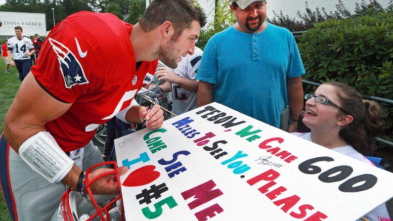 El  mariscal de campo de los Patriots, Tim Tebow, se inclina para hablar con Madelin Beardsley, fanática de la silla de ruedas, mientras firma un autógrafo con su cartel que explica lo lejos que ha llegado para intentar conocerlo. (Imagen representativa de Jim Davis/The Boston Globe via Getty Images)