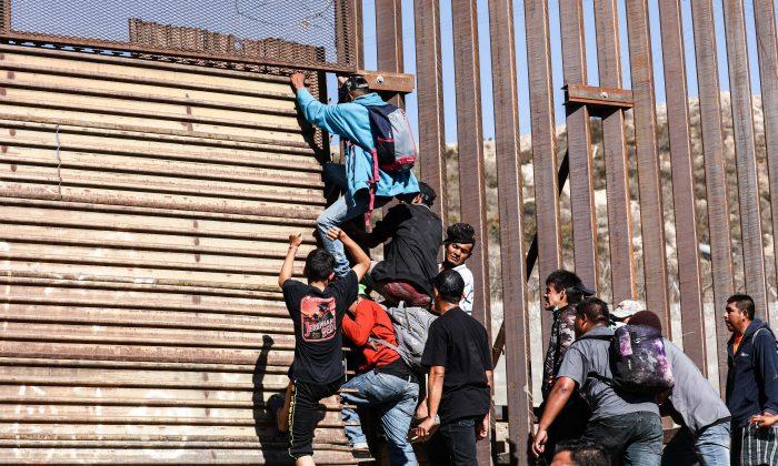 El 25 de noviembre de 2018, migrantes atraviesan la valla fronteriza de Estados Unidos justo después de la entrada peatonal al este del cruce de San Ysidro en Tijuana, México. (Charlotte Cuthbertson/La Gran Época)