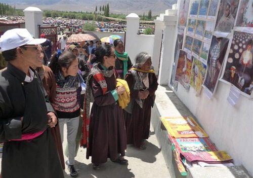 Al salir de un evento budista en la región montañosa de la India, muchos asistentes se detienen en una presentación de información sobre la persecución a Falun Dafa en China. (Crédito: Minghui.org)