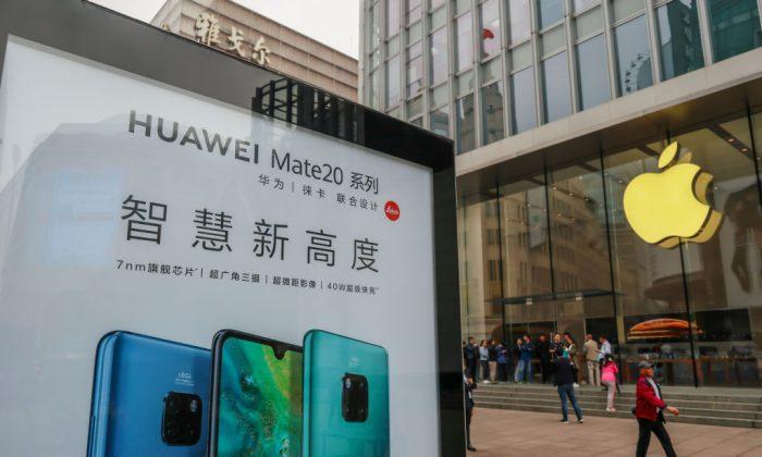 Un cartel publicitario de Huawei se exhibe frente a una tienda de Apple en Shanghai, el 26 de octubre de 2018. (STR/AFP/Getty Images)