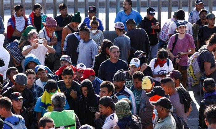 Los migrantes regresan a su campamento después de un intento fallido de colarse en la frontera de Estados Unidos y entrar ilegalmente, justo al oeste del cruce de San Ysidro en Tijuana, México, el 25 de noviembre de 2018. La valla en el fondo no es la frontera, es una valla secundaria en el lado de México. (Charlotte Cuthbertson/La Gran Época)
