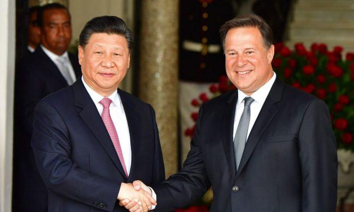 El presidente de Panamá, Juan Carlos Varela (R), y el mandatario chino Xi Jinping se dan la mano cuando este último llega al palacio presidencial en la ciudad de Panamá, el 3 de diciembre de 2018. (Luis Acosta/AFP/Getty Images)
