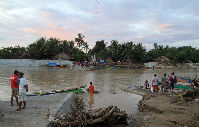 Varios aldeanos filipinos cruzan en barco después de que el camino por tierra resultara dañado y se inundara la ciudad de Bulan, en la provincia de Sorsogon, Filipinas, el 31 de diciembre de 2018. Las inundaciones y derrumbamientos provocados por la tormenta tropical Usman han causado 85 muertos y han dejado 20 desaparecidos. EFE/EPA/ROMEDOR GLORIANE