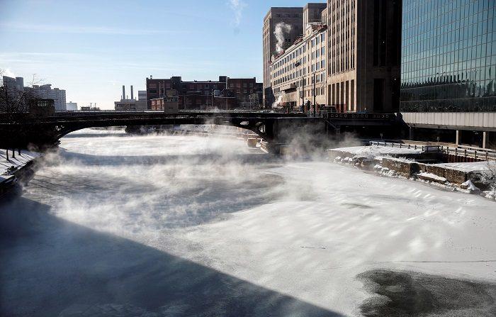 Varias personas cruzan un puente mientras la niebla se eleva desde el río Chicago, este jueves en Chicago, Illinois (Estados Unidos). EFE/ Kamil Krzaczynski
