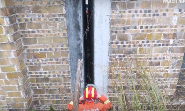 Bombero observa a un bebé chino de dos años atrapado entre dos paredes. (Captura de vídeo)