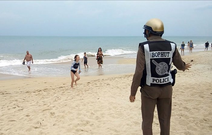 Un policía advierte a bañistas de la prohibición de baño en la playa en la isla Koh Samui debido al tiempo en la provincia de Surat Thani en Tailandia hoy, 3 de enero de 2019. Las autoridades tailandesas han pedido a la población de más de una decena de provincias del sur del país que extremen la precaución ante la llegada de la tormenta Pabuk, que se aproxima hoy al golfo de Tailandia. EFE/ Sitthipong Chareonjai