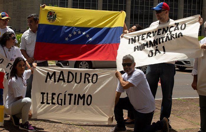 """Un grupo de venezolanos se manifiesta hoy frente a la cancillería brasileña en Brasilia (Brasil), donde pidieron al presidente del país, Jair Bolsonaro, que no les deje """"solos"""" y ejerza """"presiones"""" frente al Gobierno de Nicolás Maduro, quien inicia un nuevo mandato. (EFE/Joédson Alves)"""
