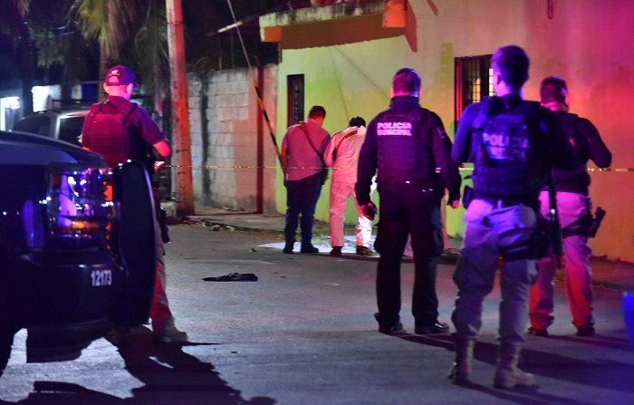 Peritos judiciales inspeccionan la zona donde se registró un ataque con armas de fuego este domingo en Cancún (México). Al menos siete personas murieron en la madrugada de hoy, en un domicilio de la región 219 de Cancún donde la concurrencia era mayormente de jóvenes que se divertían en una fiesta. EFE/Aonso Cupul