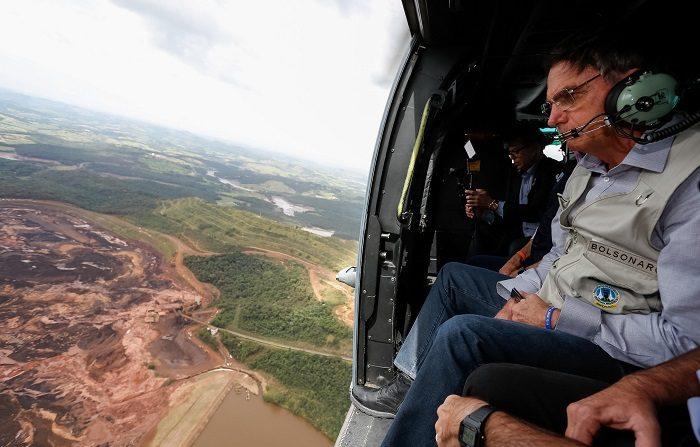 Fotografía cedida por la Presidencia de Brasil que muestra al presidente Jair Bolsonaro mientras sobrevuela la zona afectada por una avalancha tras la rotura de una represa minera, este sábado, en Brumadinho (Brasil). La rotura de la represa se presentó ayer viernes. A la mañana de hoy se han confirmado nueve muertos y cerca de 300 desaparecidos. EFE/Isac Nobrega