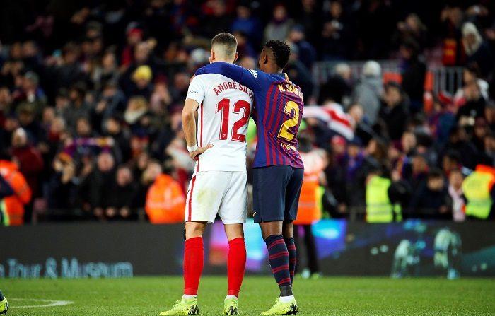 Los portugueses Andre Silva (i), del Sevilla FC, y Nélson Semedo, del FC Barcelona, al finalizar el partido de vuelta de cuartos de final de la Copa del Rey que FC Barcelona y Sevilla FC disputaron esta noche en el Camp Nou, en Barcelona. EFE/Alejandro García