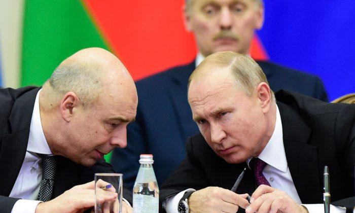 El presidente ruso Vladimir Putin (Der.) y el ministro de Finanzas Anton Siluanov conversan durante una reunión del Consejo Económico Supremo Euroasiático en San Petersburgo, el 6 de diciembre de 2018. (Olga Maltseva/AFP/Getty Images)