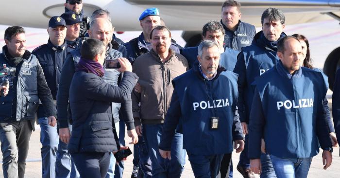 Cesare Battisti (c), miembro del grupo terrorista italiano Proletarios Armados por el Comunismo (PAC), desembarca escoltado por varios policías italianos a su llegada al aeropuerto Ciampino de Roma (Italia), el 14 de enero de 2019. EFE/Ettore Ferrari
