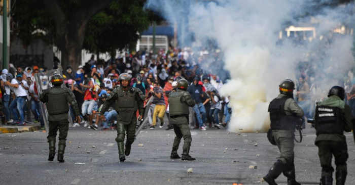 La policía se enfrenta a manifestantes durante una protesta contra el régimen de Nicolás Maduro en momentos en que el jefe de la Asamblea Nacional de Venezuela, Juan Guaidó, asumió como presidente encargado del país, en Caracas el 23 de enero de 2019. (YURI CORTEZ/AFP/Getty Images)