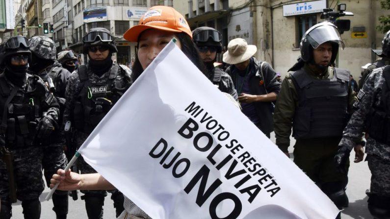 """Una joven sostiene una bandera delante de los policías que dice: 'Mi voto debe ser respetado'. Bolivia dijo """"No"""" durante una marcha contra la nominación del presidente boliviano Evo Morales como candidato a la reelección para las elecciones de octubre de 2019, durante un paro nacional, en La Paz, el 6 de diciembre de 2018. (AIZAR RALDES/AFP/Getty Images)"""