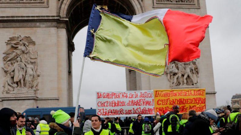 Un manifestante agita una bandera francesa parcialmente cubierta con una tela amarilla durante una manifestación antigubernamental convocada por el movimiento Chalecos Amarillos junto al Arco del Triunfo en París, el 12 de enero de 2019. (THOMAS SAMSON/AFP/Getty Images)