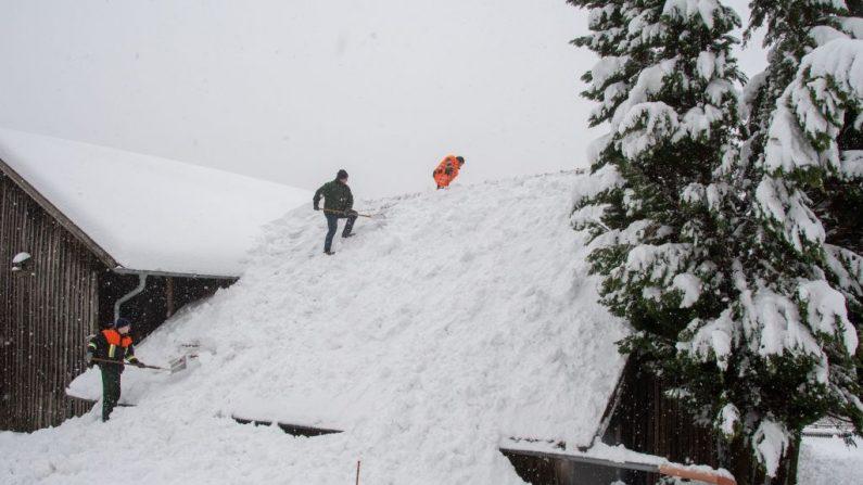 Los hombres palean la nieve desde un techo en Elisabethszell, sur de Alemania, el 13 de enero de 2019. (ARMIN WEIGEL/AFP/Getty Images)